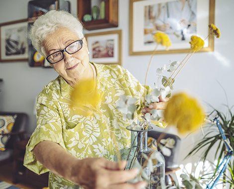 elderly woman fixing her flowers